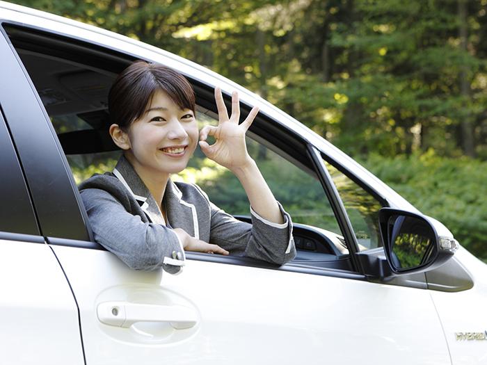 窓から乗り出してOKマークを作る笑顔の女性