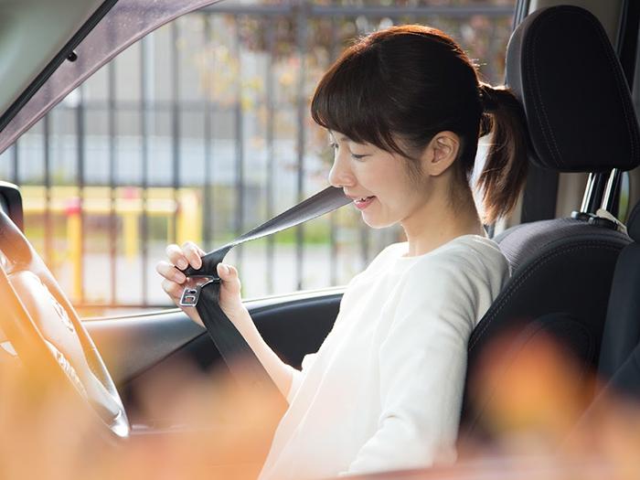 運転席に乗り、シートベルトを締める女性