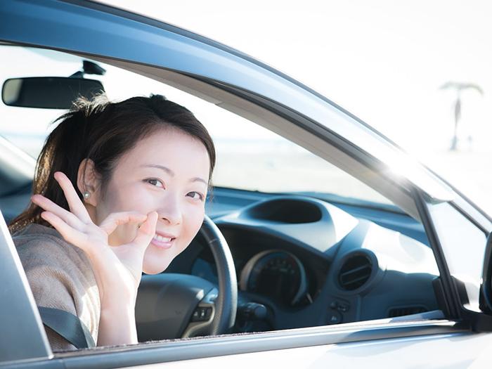 運転席に座りOKサインをする女性