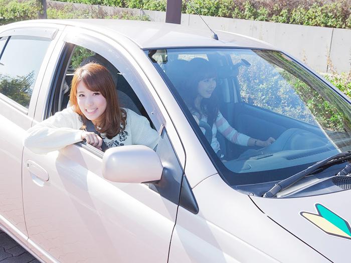 運転席から顔を出す笑顔の女性