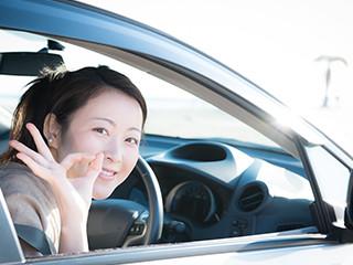 運転席からOKサインを出す女性